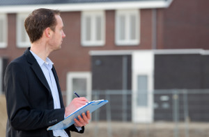 Manassas Broker making notes in front of new home